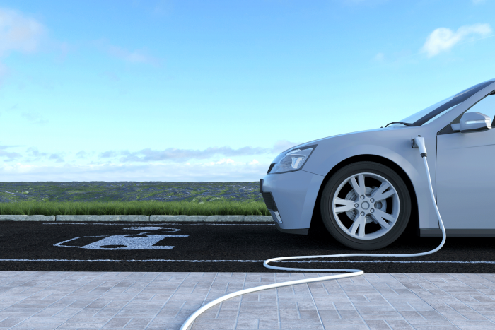 electric vehicle charging in a parking lot under blue sky